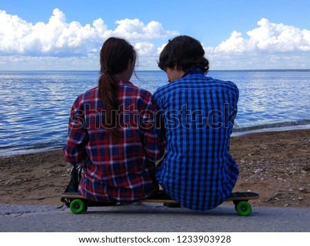 A young girl and a young guy are sitting on the beach. Two sit on a skateboard. View from the back