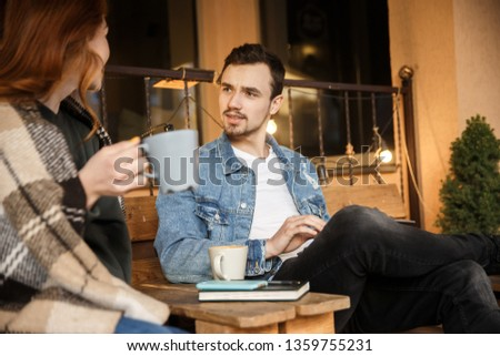 A young girl and a young man are talking. They are sitting on the cafe terrace.