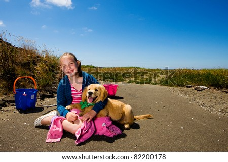 A young girl and her puppy outside