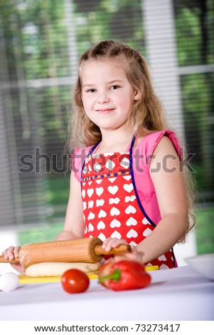 a young girl baking cakes in the kitchen