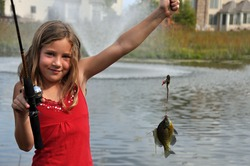 a young girl catches a fish