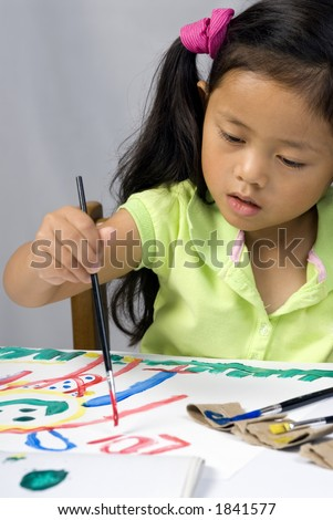 A young girl creates a self portrait with paint.