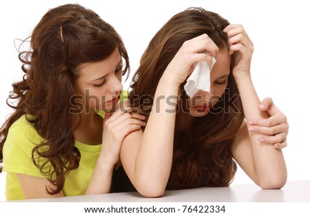 A young girl crying and a friend calming her