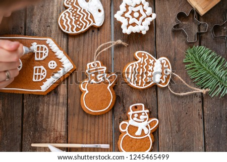 A young girl decorates ginger cookies Christmas winter morning. Woman draws Icing on honey gingerbread house. Wooden brown table. copy space. Blank biscuit gingerbread house, ready to decorate.