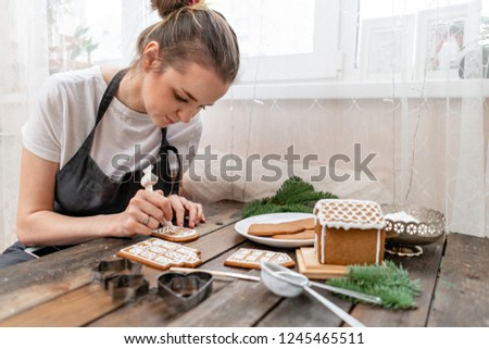 A young girl decorates ginger cookies Christmas winter morning. Woman draws Icing on honey gingerbread cookies. Wooden brown table. copy space. Blank biscuit gingerbread house, ready to decorate.
