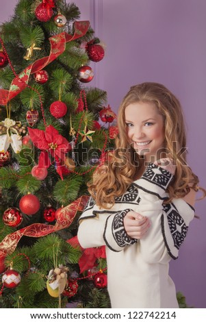 A young girl decorates the Christmas tree