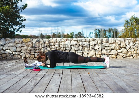 a young girl does sports exercises in a park on the yoga mat with laptop and headphones  Stok fotoğraf ©