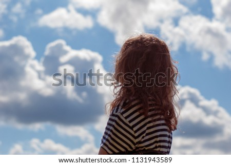 A young girl dreaming while looking at the sky