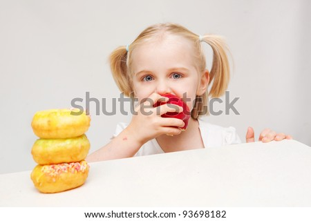A young girl enjoys a sandwich consisting of wholemeal bread.