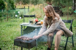 A young girl expertly prepares grilled meat on the grill to get away alone after a working week, and relax in the courtyard of a country house