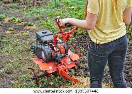 A young girl farmer in a yellow T-shirt stands in front of a small garden with a motor-cultivator and prepares to plow a vegetable garden. #1383507446
