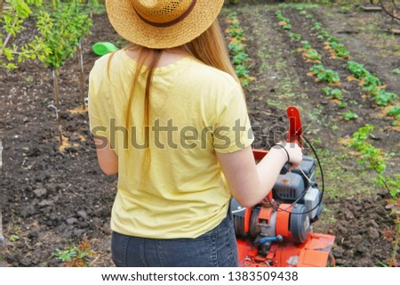 A young girl farmer in a yellow T-shirt stands in front of a small garden with a motor-cultivator and prepares to plow a vegetable garden. #1383509438