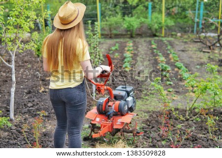 A young girl farmer in a yellow T-shirt stands in front of a small garden with a motor-cultivator and prepares to plow a vegetable garden. #1383509828