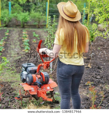 A young girl farmer in a yellow T-shirt stands in front of a small garden with a motor-cultivator and prepares to plow a vegetable garden.    #1384817966