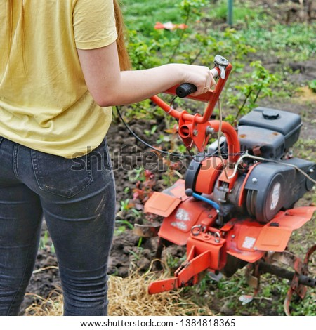 A young girl farmer in a yellow T-shirt stands in front of a small garden with a motor-cultivator and prepares to plow a vegetable garden.    #1384818365