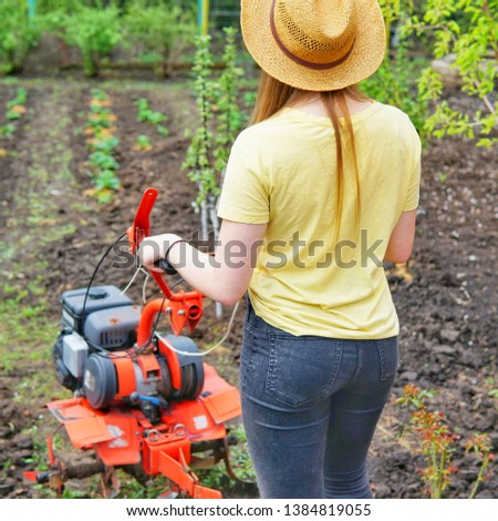 A young girl farmer in a yellow T-shirt stands in front of a small garden with a motor-cultivator and prepares to plow a vegetable garden.    #1384819055