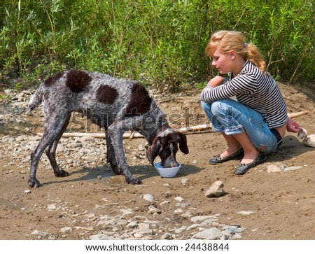 A young girl feeds a dog at river bank.