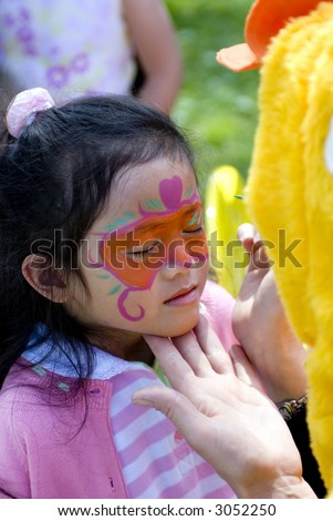 A young girl gets her face painted with bright colors.