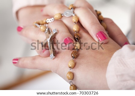 a young girl hands pray with a rosary