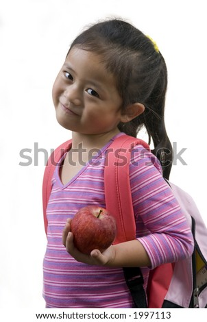 A young girl has an apple for her teacher on the first day of school