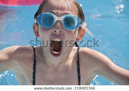 A young girl having fun in a swimming pool wearing swimming goggles.