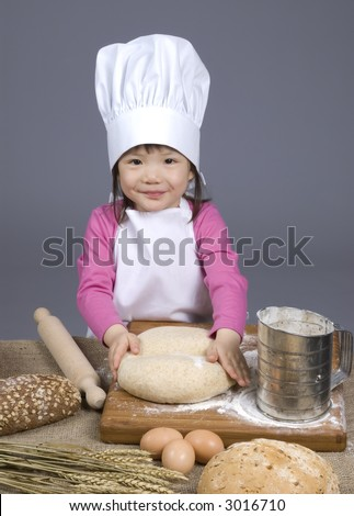 A young girl having fun in the kitchen making a mess....I mean making bread. Education, learning, cooking, childhood