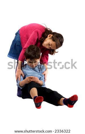 A young girl helping her brother up after he trips over and hurt his knee.