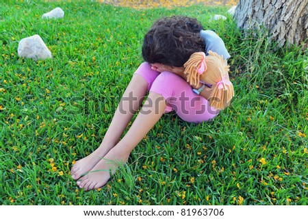 A young girl hides her face and cries under a tree on the grass while holding her stuffed toy doll.