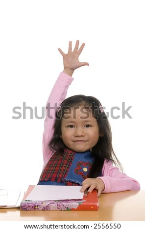 A young girl hold her hand high in the air... pick me I know