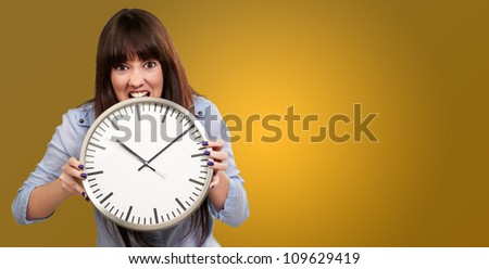 A Young Girl Holding A Clock And Angry On Yellow Background