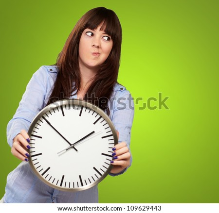 A Young Girl Holding A Clock And Making Face On Green Background