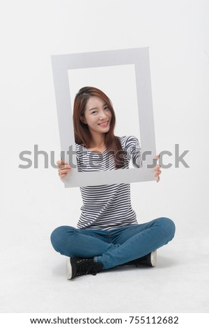 A young girl holding a picture frame.
