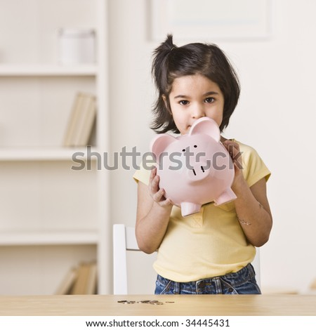 A young girl holding a pink piggy bank.  Square framed shot.