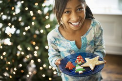 A young girl holding a plate of organic decorated Christmas cookies
