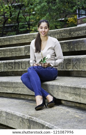 A young girl, holding a white rose and sitting on stairs, is smilingly looking at you/Portrait of Young Girl