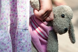 A young girl holds a soft toy rabbit