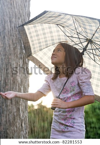 A young girl holds an umbrella during a brief rain shower.