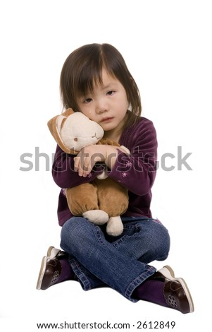 A young girl hugs here bunny as she cries.