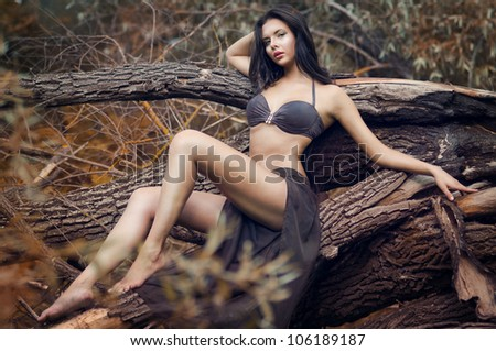 A young girl in a beautiful bathing suit standing on a fallen tree, portrait series of girls in nature