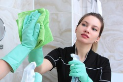 A young girl in a black uniform cleans the bathroom mirror. The man is out of focus. The bathroom is fitted with marble tiles.
