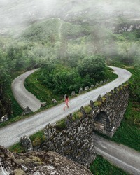 A young girl in a dress runs across a bridge in the mountains of Norway. Road in the mountains with fog. Tourism active life and adventures.