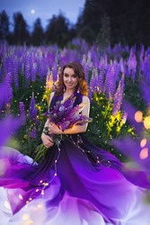 A young girl in a gradient haute couture dress in black, purple and white colors standing among a blooming lupine field in the evening twilight.