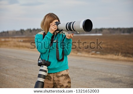 A young girl in a green sweater and camouflage pants takes pictures on a professional camera with a long-focus lens on the background of the road. On the neck hangs another