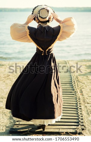 A young girl in a hat, standing full-length with her back to the camera, in a retro dress, holding her hat with her hands. Historical reconstruction Stockfoto ©