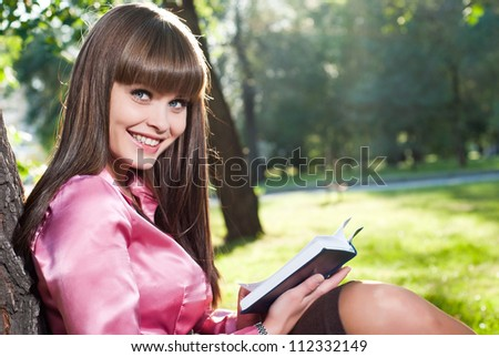 A young girl in a park, reading a book