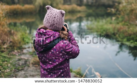 A young girl in a purple jacket and hat walks with a camera and takes pictures of nature in the fall. Baby photographer. Happy childhood. Portrait and photography.