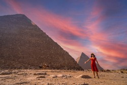 A young girl in a red dress at the pyramid of Cheops the largest pyramid at sunset. The pyramids of Giza the oldest funerary monument in the world. In the city of Cairo, Egypt