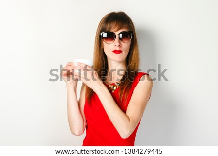 A young girl in a red dress holds in her hand a cup of coffee on a light background. Coffee shop concept, breakfast. #1384279445