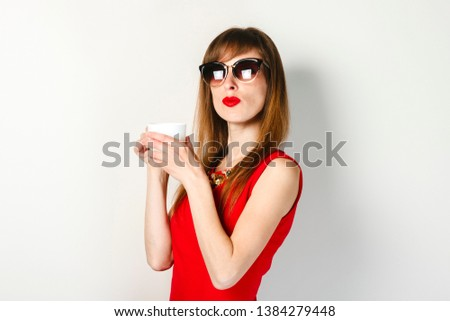 A young girl in a red dress holds in her hand a cup of coffee on a light background. Coffee shop concept, breakfast. #1384279448