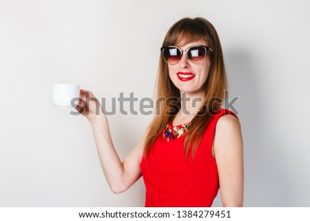 A young girl in a red dress holds in her hand a cup of coffee on a light background. Coffee shop concept, breakfast. #1384279451